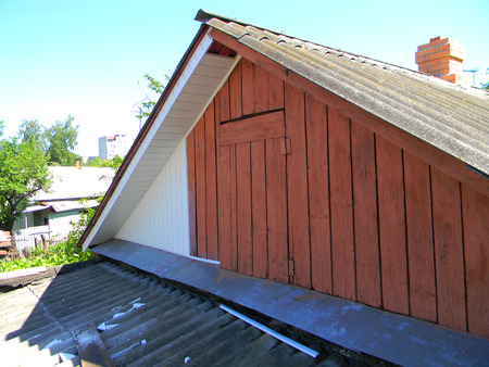 Old house with asbestos roof renovation with plastic siding installation.