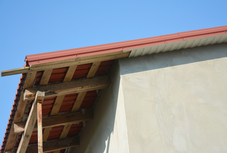 Metal roofing construction with unfinished eaves, fascia board, soffits.
