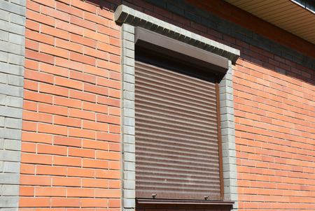Brick house window with rolling shutter for house protection.