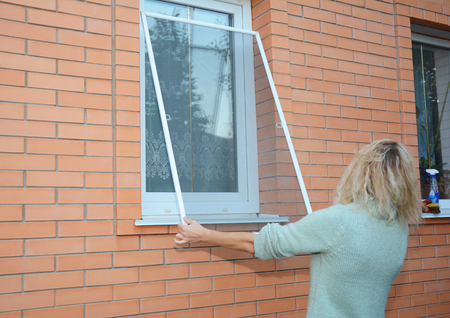 Woman installing mosquito wire screen on  house window. Zdjęcie Seryjne