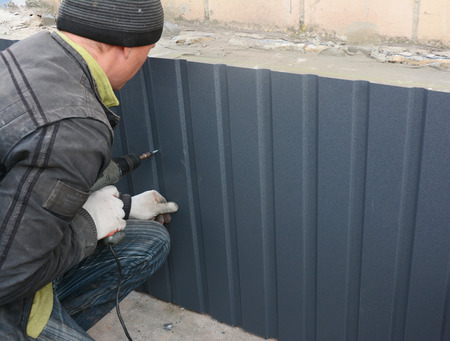 Foundation wall repair and renovation with metal sheets for waterproofing and protecting from rain.