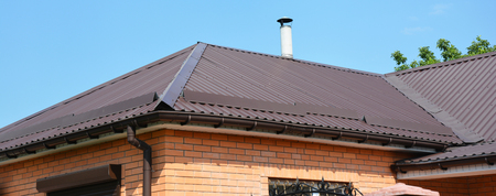 Problem areas for metal roof and rain gutter waterproofing. Guttering, gutters, metal roofing house panorama Stock Photo