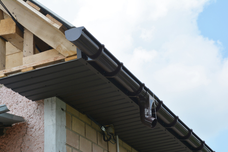 Installing soffit boards and plastic roof gutter.