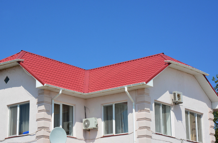 House red metal roofing with roof gutter. Stock Photo