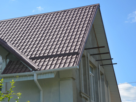 Close up on red metal roof with white, plastic rain gutter system. Roofing Construction. Stock Photo