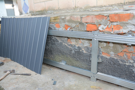 Foundation wall repair and renovation  with installing metal sheets for waterproofing and protect from rain. Stock Photo