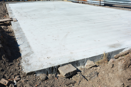 Slab-on-grade foundation on house construction site. Monolithic slabs are foundation systems constructed as one single concrete pour that consists of a concrete slab. 免版税图像
