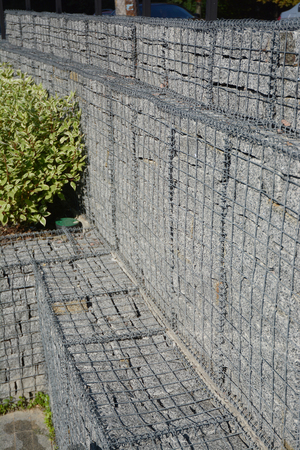 Modern gabion fence wall with stones in wire mesh. Gabion wire mesh fencing with natural stones.