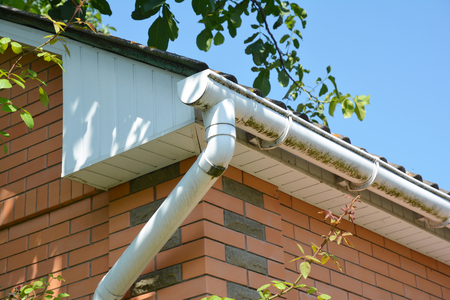 Close up on white plastic rain gutter. House roof guttering repair. Stock Photo