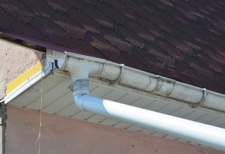 Broken roof gutter needs to repair. Close up on rain gutter damage on house asphalt shingles roof. Stock Photo