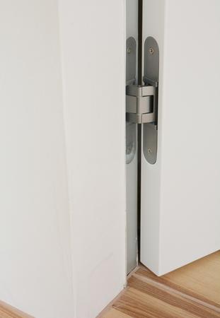 Stainless door hinges on white  swing door for interior design. Modern door hinge. Stock Photo