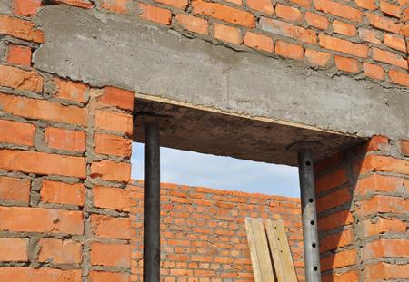 Concrete door lintel installation with metal holders. Door concrete lintel on brick unfinished house construction.