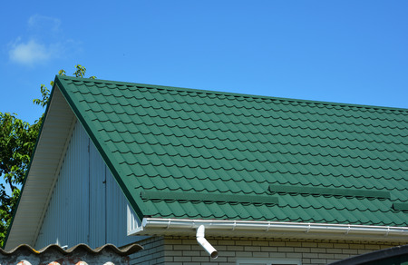 Close up on green metal roof with white, plastic rain gutter system. Roofing Construction. Stock Photo