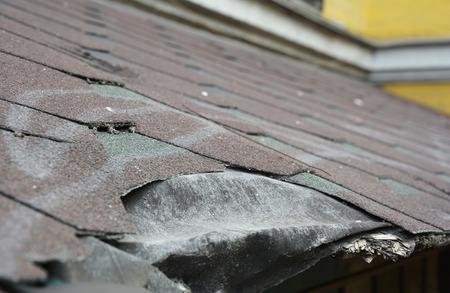 Daños en las tejas de asfalto. Tejas de asfalto para techos. Reparación de tejas de techo dañadas. Foto de archivo