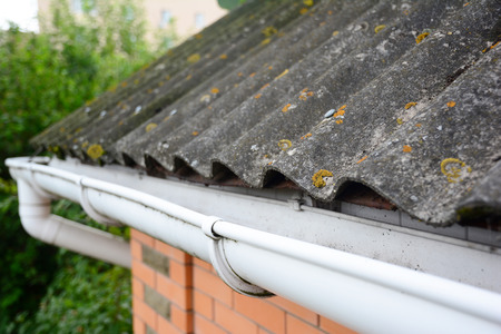House asbestos roof with close up gutter holder and plastic roof gutter pipe. Guttering.
