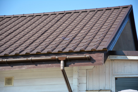 Rain gutter system. Metal roof with plastic roof guttering.