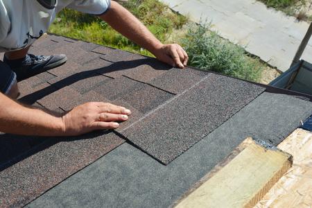 Dachdecker, der Asphaltschindeln an der Dachecke des Hausbaus installiert. Dachkonstruktion. Dachdecker verlegen Dachziegel. Standard-Bild