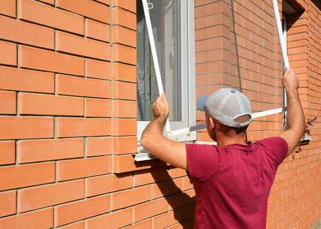Mosquito wire screen installation. Contractor installing mosquito wire screen on house window to protect from insects. Banque d'images