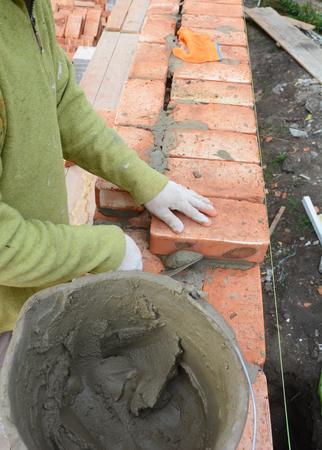 Bricklayer bricklaying brick house wall.