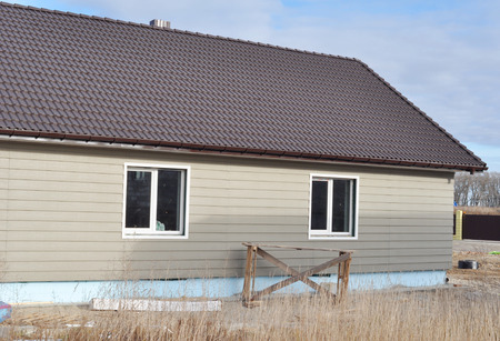 Siding house installation with clay tiles roof, guttering and unfinished house plastic foundation insulation