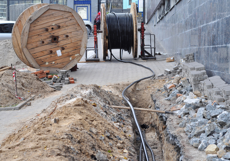 Wooden coil of electric cable and optical fibres in the digging trench on the construction site