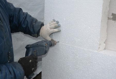 Wall Insulation. Builder drilling wall for installing anchors to hold rigid insulation foam board. Attach rigid foam insulation to a concrete wall