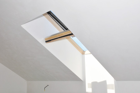 Attic house skylight window after room repair and renovation with painting and plastering wall. 免版税图像