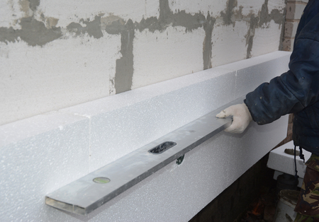 Builder install plastic insulation board and measuring with spirit level. Exterior Foam Insulation.