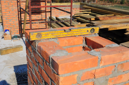 Building brick chimney on new house construction.