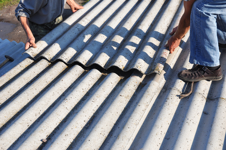 Asbestos roofing construction. Roofers installing asbestos roof sheets.