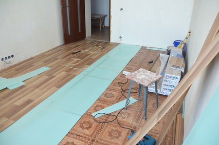 KYIV, UKRAINE - September, 12, 2018: Installing laminate flooring with insulation board in empty room. Standard-Bild - 119373784