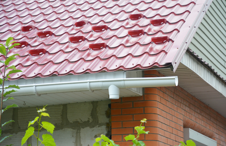 Rain gutter downspout drain pipe installation with metal roof snow board protection. Stock Photo