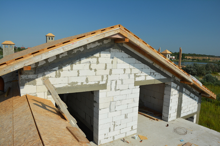 Roofing construction with trusses, wooden beams on new house building. Rooftop view. Фото со стока