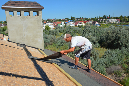 KYIV, UKRAINE - September, 12, 2018: Roofer contractor laying and installing asphalt shingles. Roofing construction with roof tiles, asphalt shingles.
