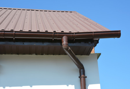 House metal roof corner with plastic rain gutter pipeline system.