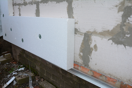 Builder installing anchors in house wall for rigid insulation foam. 스톡 콘텐츠