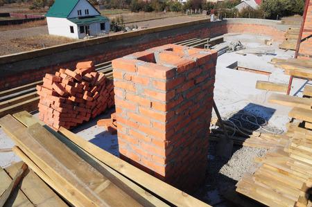 Building chimney from bricks. Bricklaying new house chimney