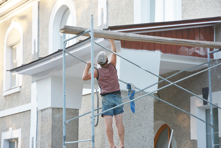 Worker installing house fascia boards and soffit outdoors Stock Photo