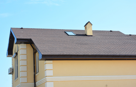 House roofing construction with asphalt shingles and skylight window.