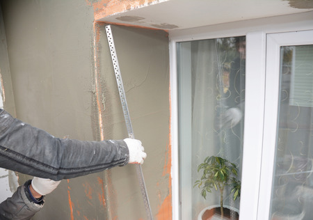 Fiber mesh contractor plastering wall with putty knife;
