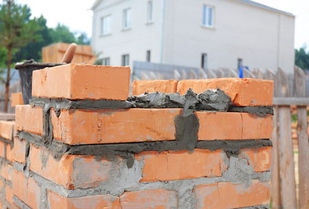 Bricklaying house brick wall. Close up on laying bricks with concrete. Stock Photo