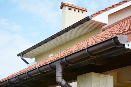 Rain gutters system  on new house with chimney, red clay tiled roof and gable and valley type of roof construction