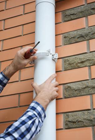Guttering. Contractor installing rain gutter downspout drain pipe.