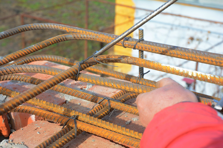 Building contractor reinforcement corner concrete bars with wire rod. Builder making iron bars lintels  for house construction.