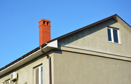 House with metal roof, brick chimney, rain gutter and insulate plaster wall outdoors.