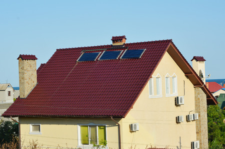 Modern house roof with solar water heater panels and air conditioner compressors for energy efficiency. Stockfoto