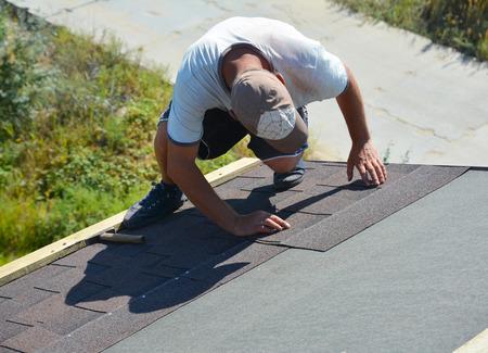 Roofer installing Asphalt Shingles  on house construction roof. Shingles roofing construction. Banque d'images - 120927353