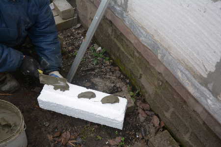 External house wall insulation. Foam Sheathing. Builder installing plastic board with glue and concrete.