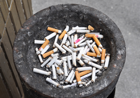 KYIV, UKRAINE - December, 04, 2018:  Lot of  cigarette butts  laying in garbage bin. Cigarette butts.