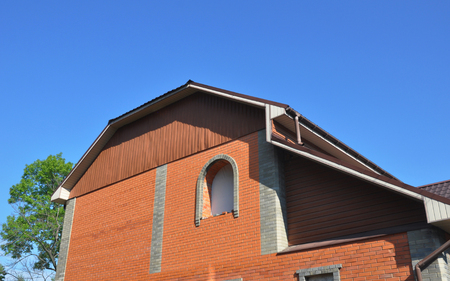 House mansard roof with brick wall, unfinished window installation,  rain gutters.